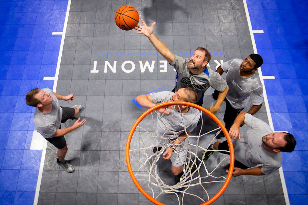 Paul Camp (top) reaches for a rebound during a basketball game with, Kevin Mezger (left), Micah Cunningham (bottom), David Levias (top right) and Joey Johnson (bottom right) at Ridgemont Commercial Construction in August.