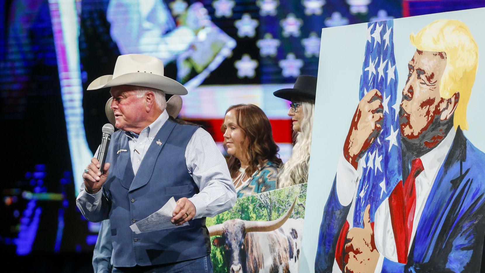 El comisionado de Agricultura de Texas, Sid Miller, realiza una subasta de una pintura del expresidente Donald Trump durante la convención republicana llevada a cabo el fin de semana en Dallas.