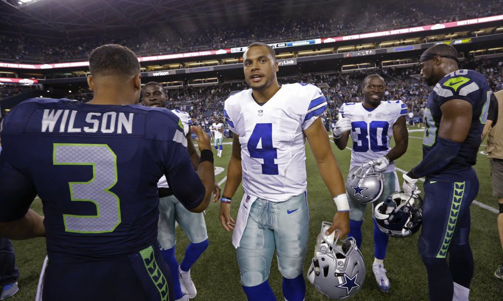 Dallas Cowboys quarterback Dak Prescott (4) talks with Seattle Seahawks quarterback Russell Wilson (3) and other players after a preseason NFL football game Thursday, Aug. 25, 2016, in Seattle. The Seahawks won 27-17. (AP Photo/Elaine Thompson)