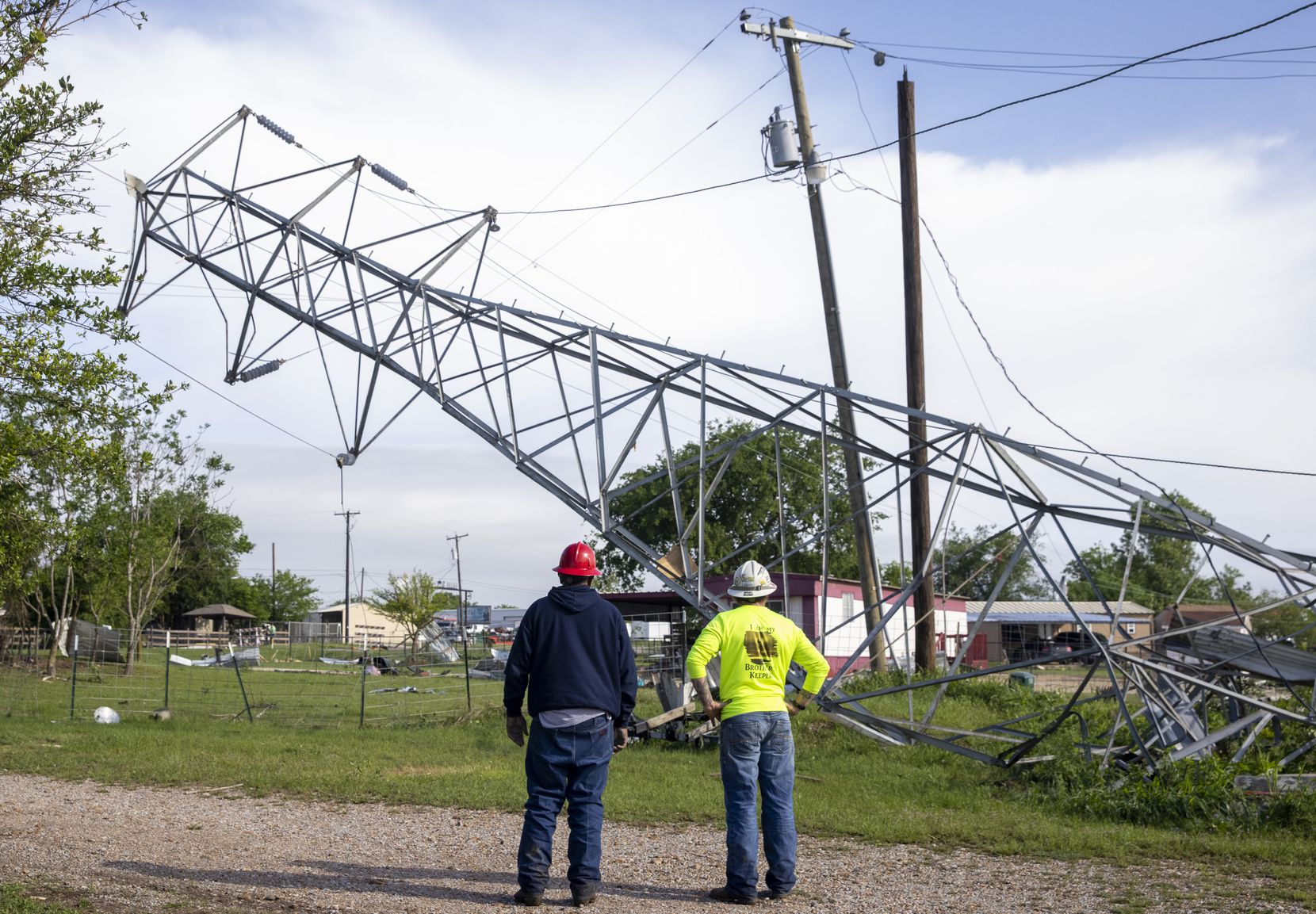 Oncor personnel survey a downed power structure where a Monday night tornado touched down just south of Waxahachie, Texas, on Tuesday, May 4, 2021. (Lynda M. González/The Dallas Morning News)
