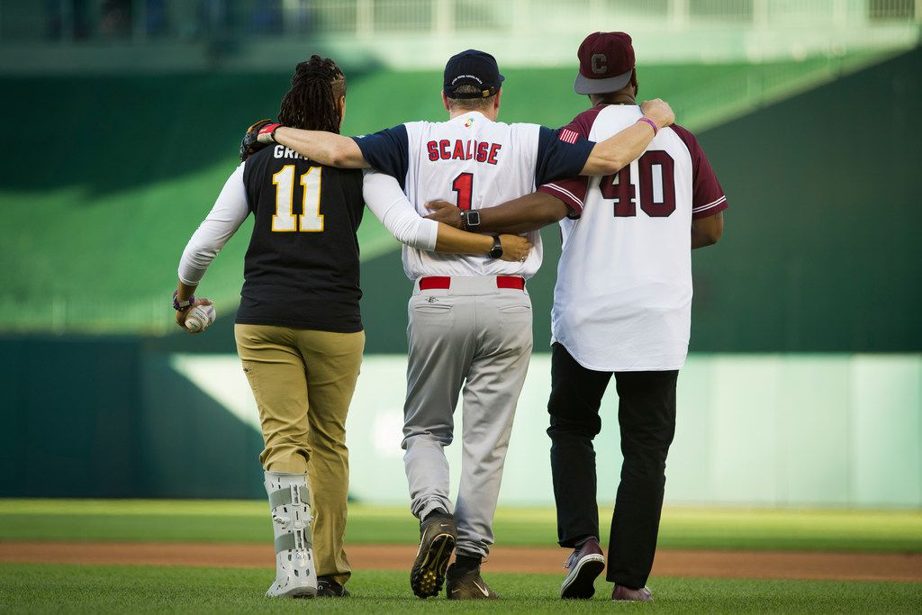 Capitol Police Special Agents Crystal Griner, left, and David Bailey, right, assist U.S. Rep. Steve Scalise to his position at second base at the start of the 57th Congressional Baseball Game at National's Park in Washington, Thursday, June 14, 2018. On June 14, 2017, Scalise was wounded in the leg when he and other Congressional members were the victims of a shooting at the baseball field they were practicing on in Alexandria, Va.