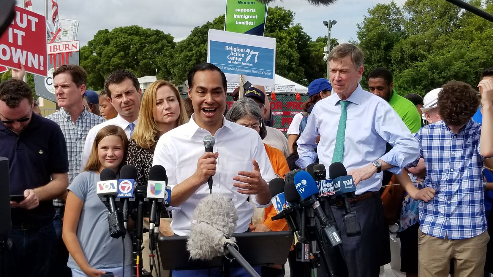 Julián Castro speaks to news media outside the migrant detention center in Homestead, Fla.. Behind him are two other presidential candidates, Pete Buttigieg (left) and John Hickenlooper, each in a shirt and tie.