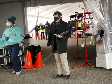 Dallas County Health and Human Services director Dr. Philip Huang checks on the  COVID-19 vaccination drive-through lanes set up at Fair Park in Dallas on Wednesday, Feb. 10, 2021.