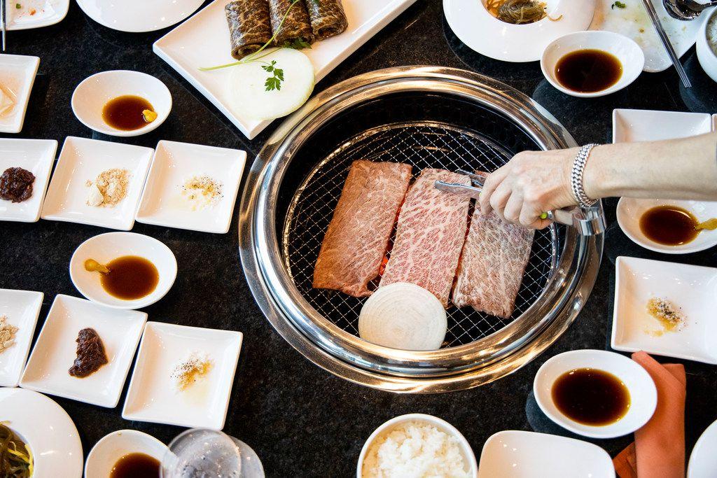 Sammantha Kang adjusts beef short ribs at K's House, a Korean restaurant in Trinity Groves, in Dallas.