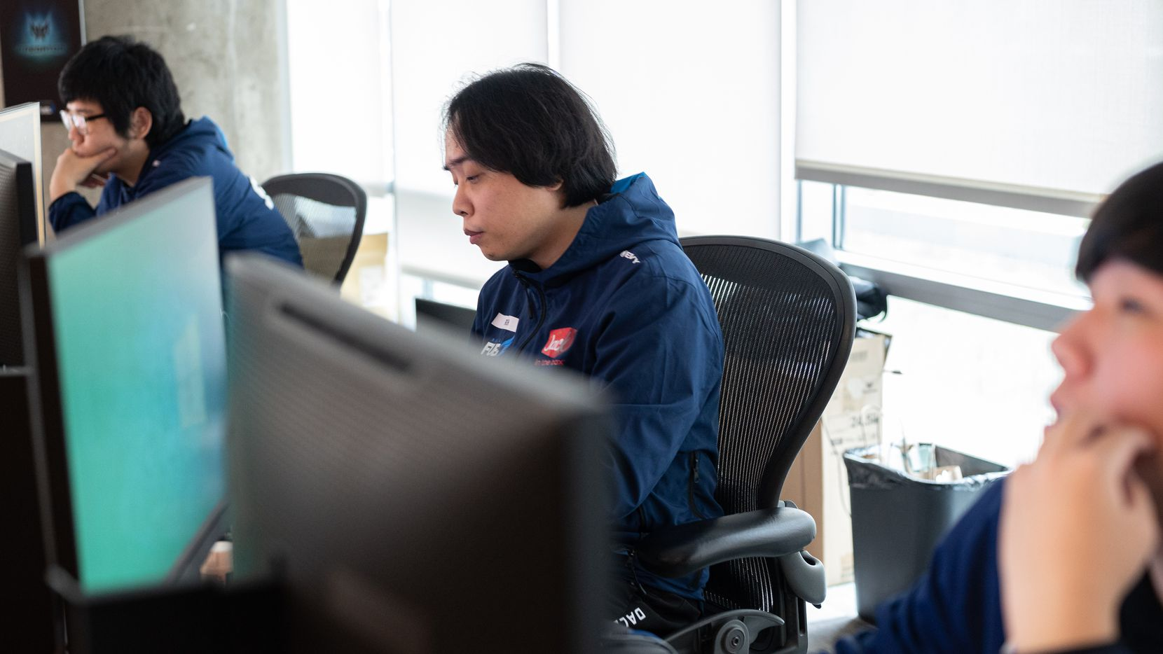 """Dallas Fuel head coach Hee-Won """"Rush"""" Yun, center, studies game play on computer monitors during practice time at the Dallas Fuel headquarters in Dallas, on Monday, Sept. 13, 2021."""