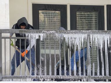 Workers clear debris from a balcony covered in icicles in the Camden Victory Park apartments after a winter storm brought snow and continued freezing temperatures to North Texas. Crews were gutting apartments that were flooded by a broken pipe for fire sprinklers.