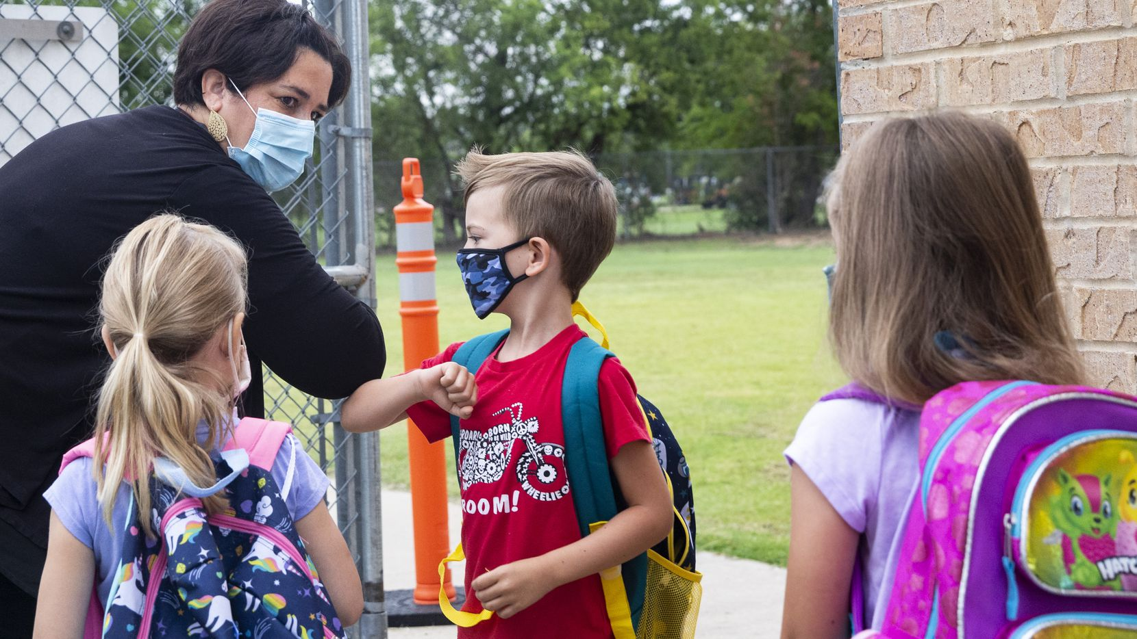Administrative Assistant Erin Johnston, left, gives an elbow bump to kindergarten student Jack Lewis during morning drop-off at Carrie L. Lovejoy Elementary School in Allen, Texas, on Wednesday, Sep. 9, 2020.