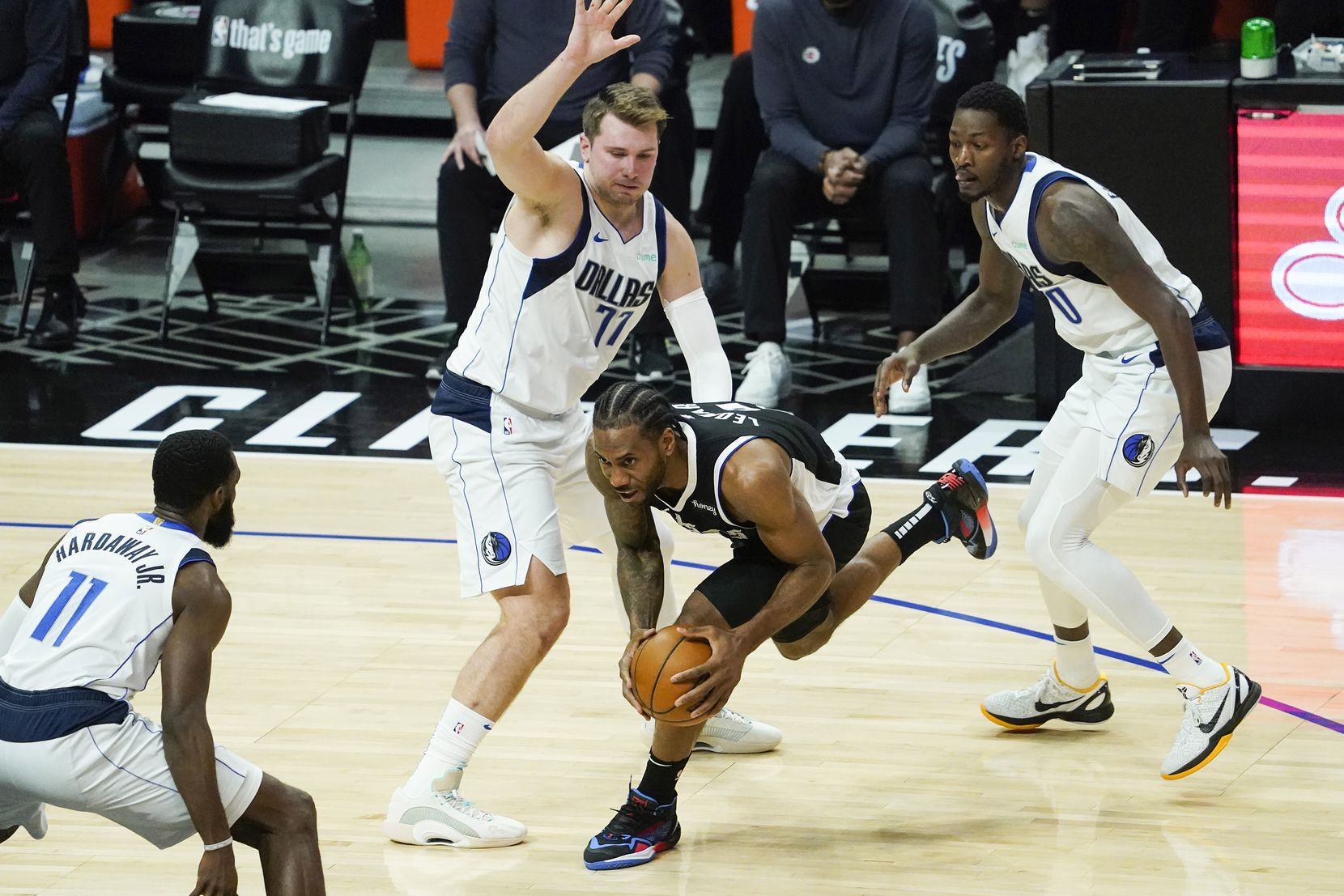 LA Clippers forward Kawhi Leonard (2) tries to drive between Dallas Mavericks guard Luka Doncic (77) and forward Dorian Finney-Smith (10) during the second quarter of an NBA playoff basketball game at the Staples Center on Wednesday, June 2, 2021, in Los Angeles.  (Smiley N. Pool/The Dallas Morning News)
