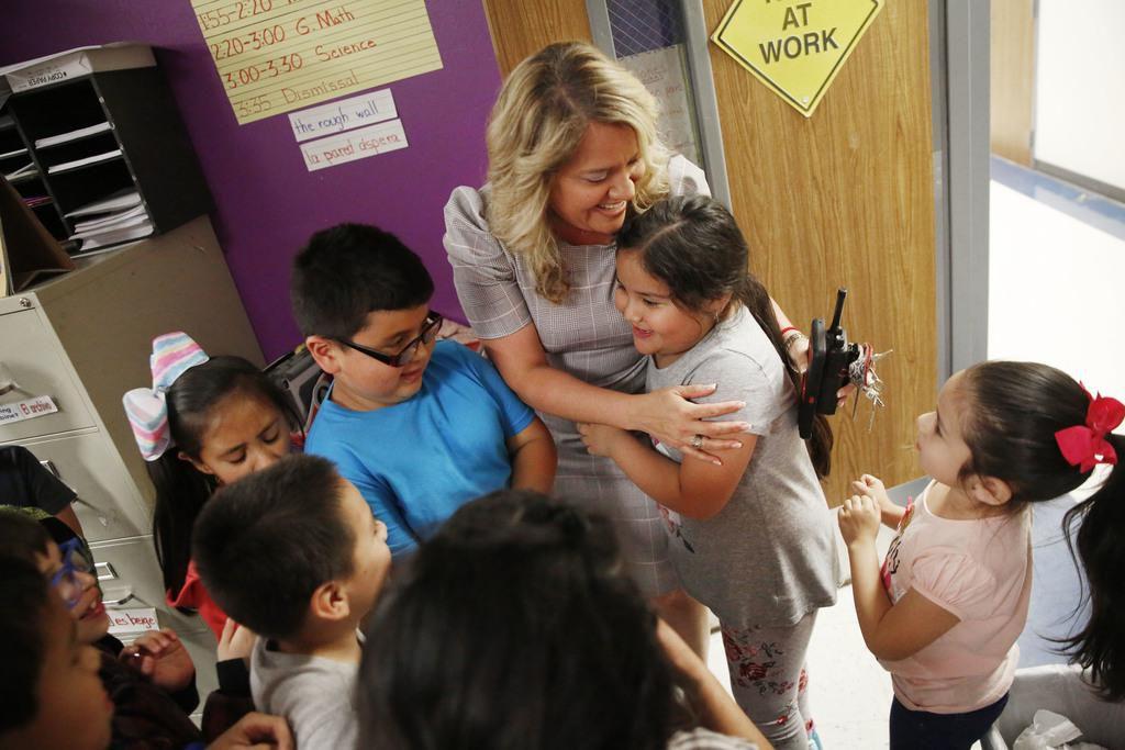 Aaliyah Miranda se abraza con algunos de sus estudiantes de la primaria Seguín en Grand Prairie, de la cual es directora interina. Hace 20 años, Miranda sobrevivió a una relación abusiva y ahora es una defensora de mujeres que pasan por lo mismo. (DMN/ROSE BACA)