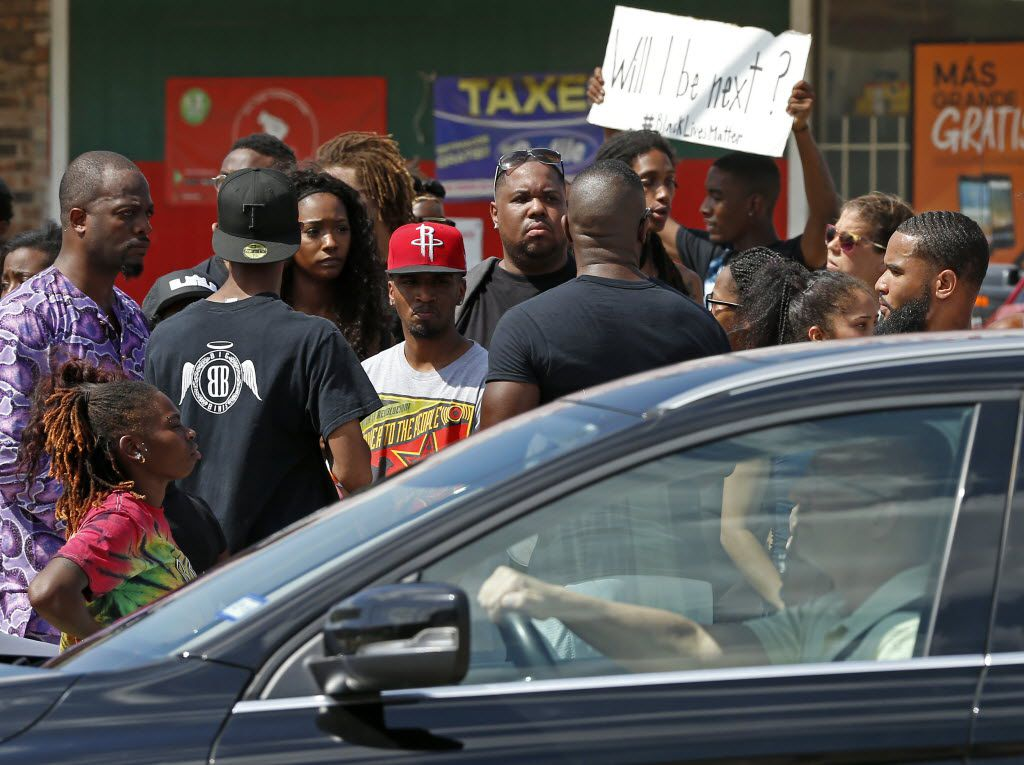 A motorist passes by a Black Lives Matter protest on park Lane in Dallas, Sunday, July 10, 2016. (Jae S. Lee/The Dallas Morning News)