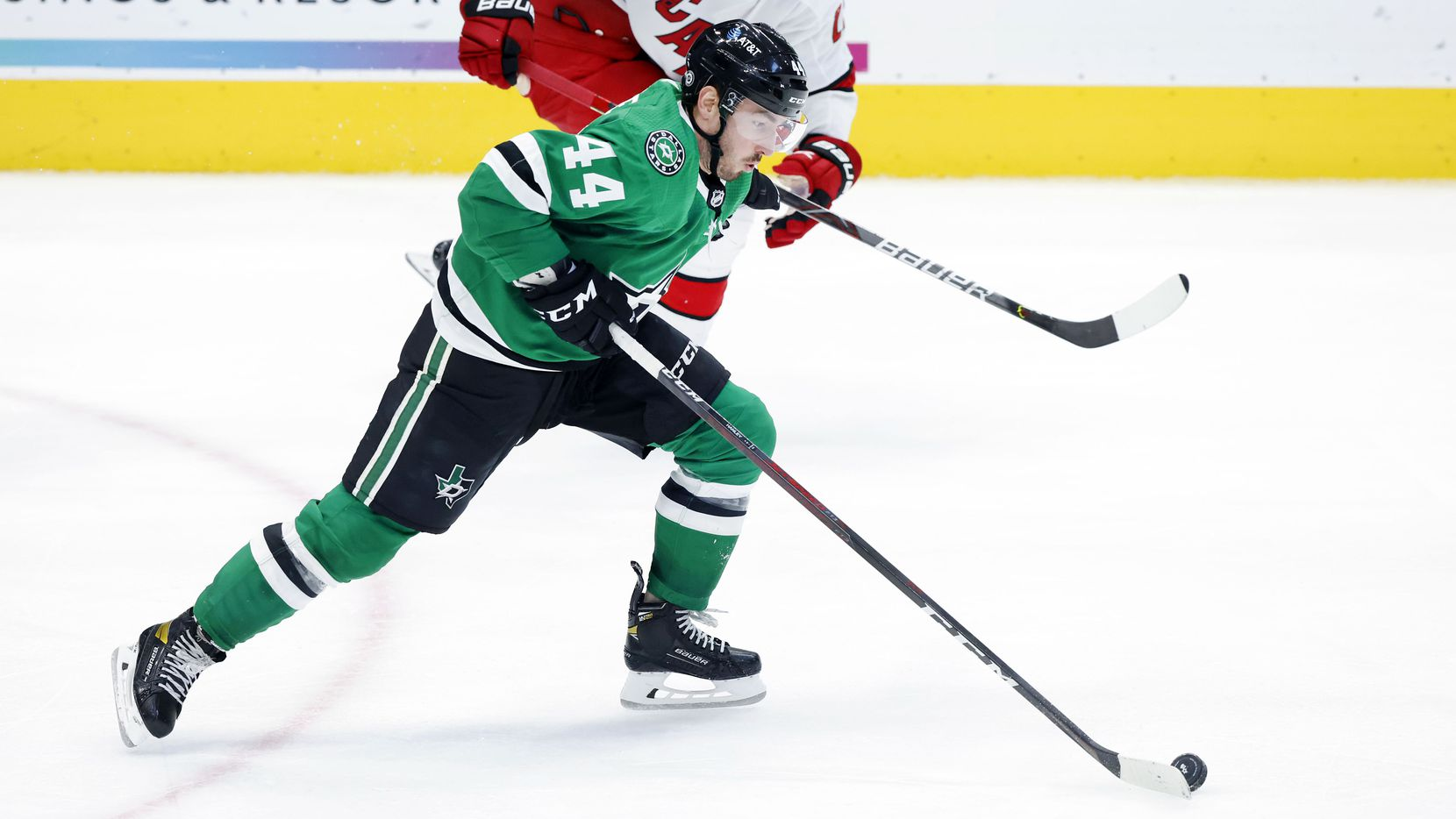 Dallas Stars defenseman Joel Hanley (44) races with the puck as Carolina Hurricanes right wing Nino Niederreiter (21) gives pursuit during the third period at the American Airlines Center in Dallas, Tuesday, April 27, 2021. The Stars lost, 5-1.