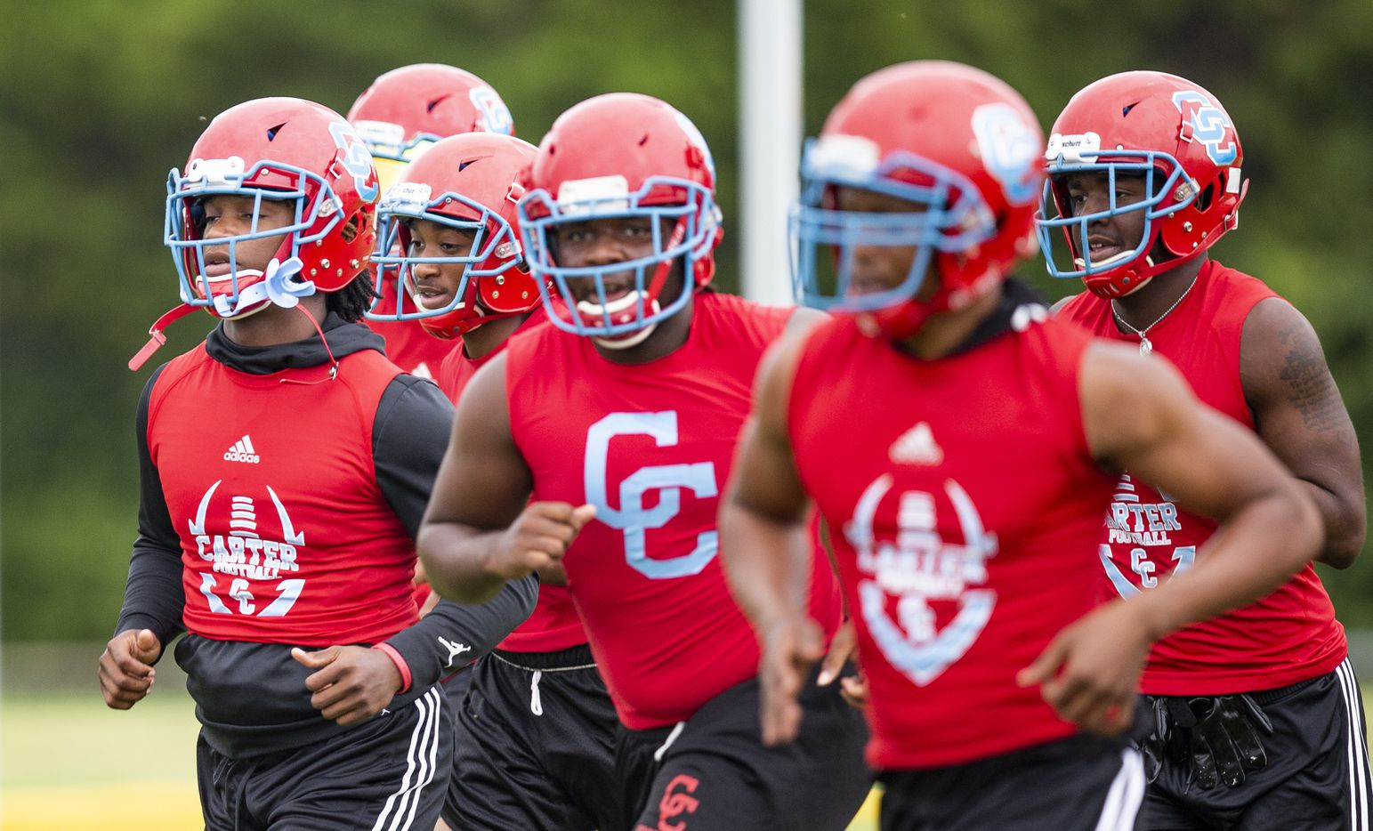 Carter senior linebacker Janari Hyder, left, and his teammates run drills during the first day of football practice at Carter High School in Dallas, Monday, August 2, 2021. (Brandon Wade/Special Contributor)
