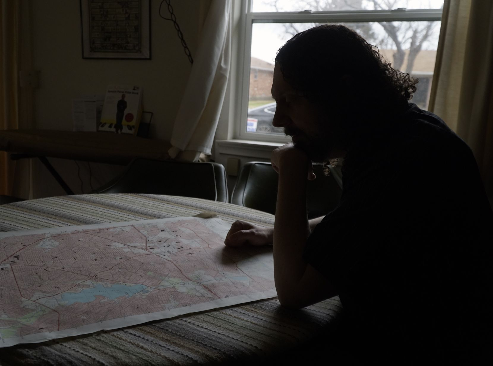 "Milazzo looks over a topographic map at his home. ""We're out there in the field, looking for authors or works that haven't come to people's attention before,"" he says of his new publishing effort."