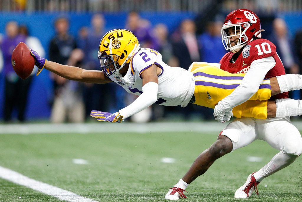 FILE - LSU wide receiver Justin Jefferson (2) extends for a touchdown while Oklahoma safety Pat Fields (10) attempts to tackle him during the first half of the Peach Bowl in Atlanta on Saturday, Dec. 28, 2019.