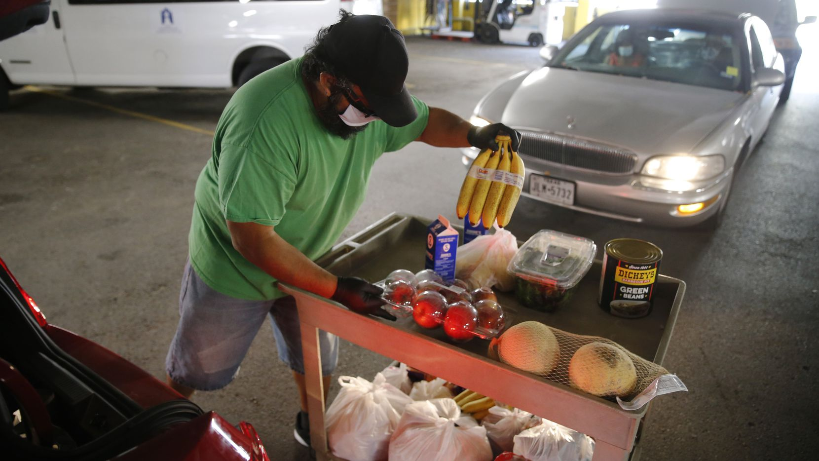 Oscar Espinosa works on putting food in a vehicle during a drive-through food distribution at The Stewpot on Friday, November 13, 2020 in Dallas. Each vehicle gets 95-110 pounds of food.