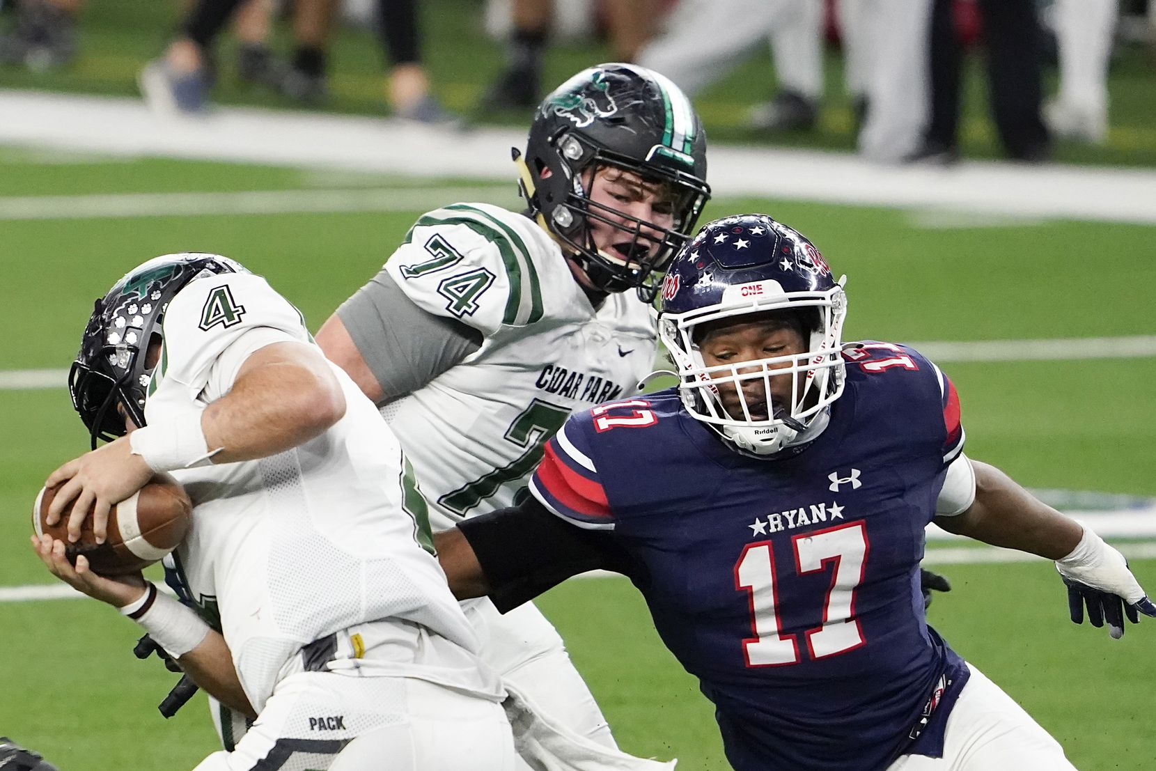 Cedar Park quarterback Ryder Hernandez (4) tries to spin away from Denton Ryan defensive lineman Michael Gee (17) during the second half of the Class 5A Division I state football championship game at AT&T Stadium on Friday, Jan. 15, 2021, in Arlington, Texas. Ryan won the game 59-14. (Smiley N. Pool/The Dallas Morning News)