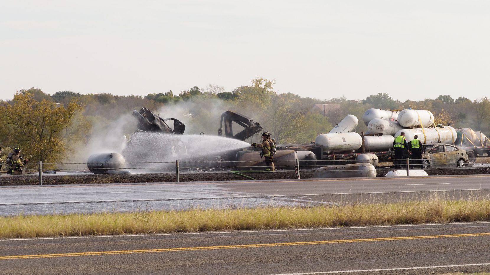 Firefighters contain a fire from a vehicle accident which caused at least three people to be killed Friday afternoon in an explosion involving two semis and three passenger vehicles in the 2300 block of Interstate 35W, Denton police said, Friday, November 8, 2019, in Denton, Texas.
