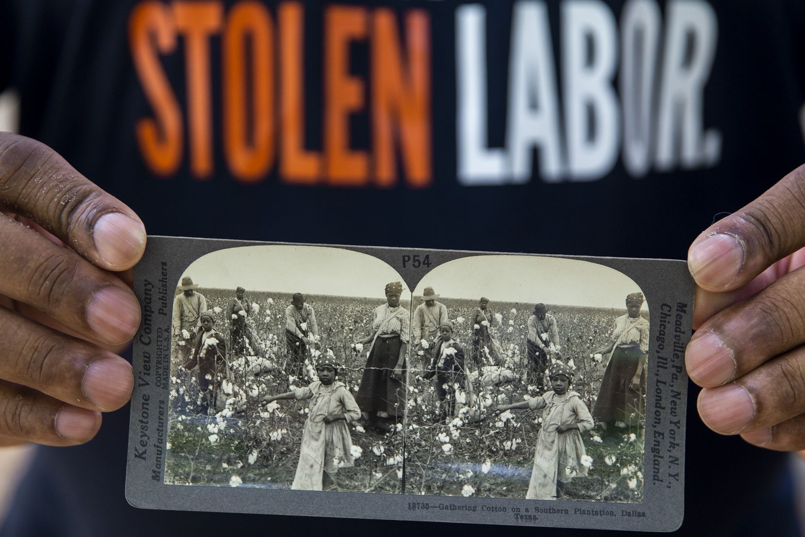 Dallas Truth, Racial Healing and Transformation executive director Jerry Hawkins holds a stereo card depicting laborers (possibly enslaved persons) gathering cotton on a plantation in Dallas (date unknown).