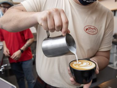 Noah Irby pours milk into a cappuccino at Wayward Coffee, the shop he opened with Trevin Willison on Friday, May 29, 2020, in Oak Cliff in Dallas. Irby is 21 years old and Willison is 22.