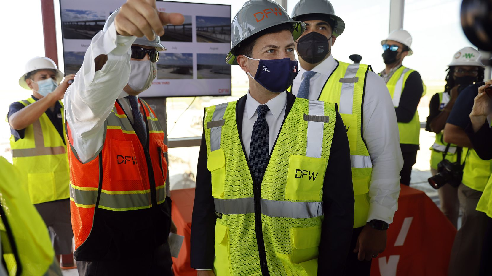 DFW Airport Executive Vice President of Infrastructure and Development Khaled Naja (left) points out construction features to U.S. Transportation Secretary Pete Buttigieg (right) as they tour building sections of the new Terminal C remodel at DFW International Airport. He came to see and hear how the Bipartisan Infrastructure Deal's investments in jobs,airports and transit will benefit the area, Wednesday, August 11, 2021. (Tom Fox/The Dallas Morning News)