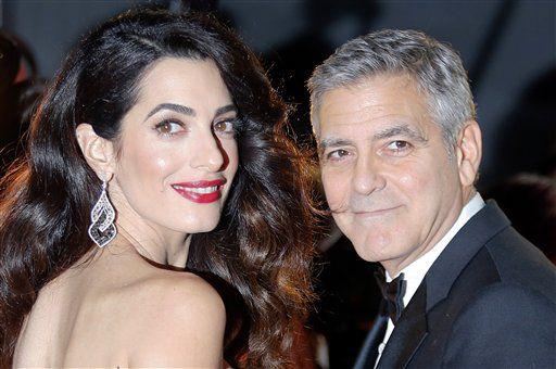 """En esta foto del 24 de febrero del 2017, el actor George Clooney y su esposa, la abogada de derechos humanos Amal Clooney, llegan a la ceremonia de los premios César del cine francés en París. George Clooney dijo en un comunicado el viernes 28 de julio del 2017 que los fotógrafos que capturaron imágenes de él y su esposa acunando a sus mellizos recién nacidos serán """"perseguidos con todo el rigor de la ley"""". (AP Foto/Francois Mori, Archivo)"""