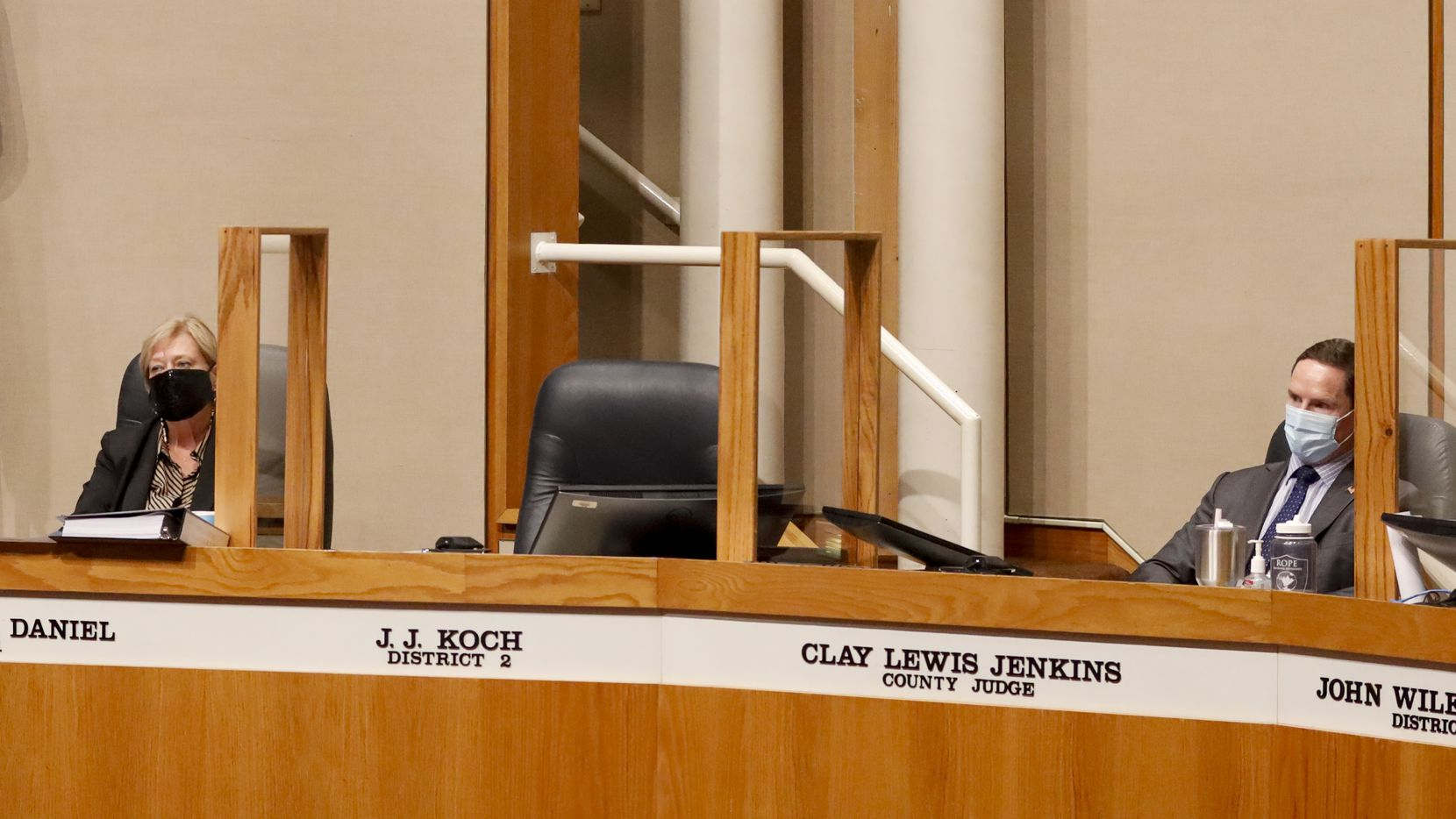 Dallas County Judge Clay Jenkins (right) and County Commissioner Theresa Daniel sit next to the empty chair of County Commissioner J.J. Koch during a Dallas County Commissioners Court meeting on Aug. 3, 2021, in Dallas. Koch was escorted from the meeting for refusing to wear a mask.