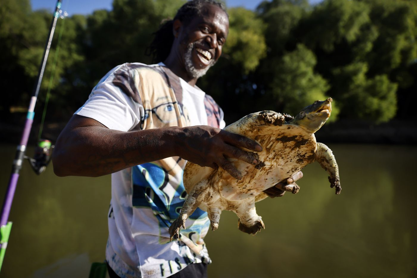 Odell Allen laughs after he reeled in a softshell turtle instead of an alligator gar on the Trinity River near the Westmoreland bridge, Monday, August 30, 2021.  He released it back to the river like he does the alligator gar he catches.  (Tom Fox/The Dallas Morning News)
