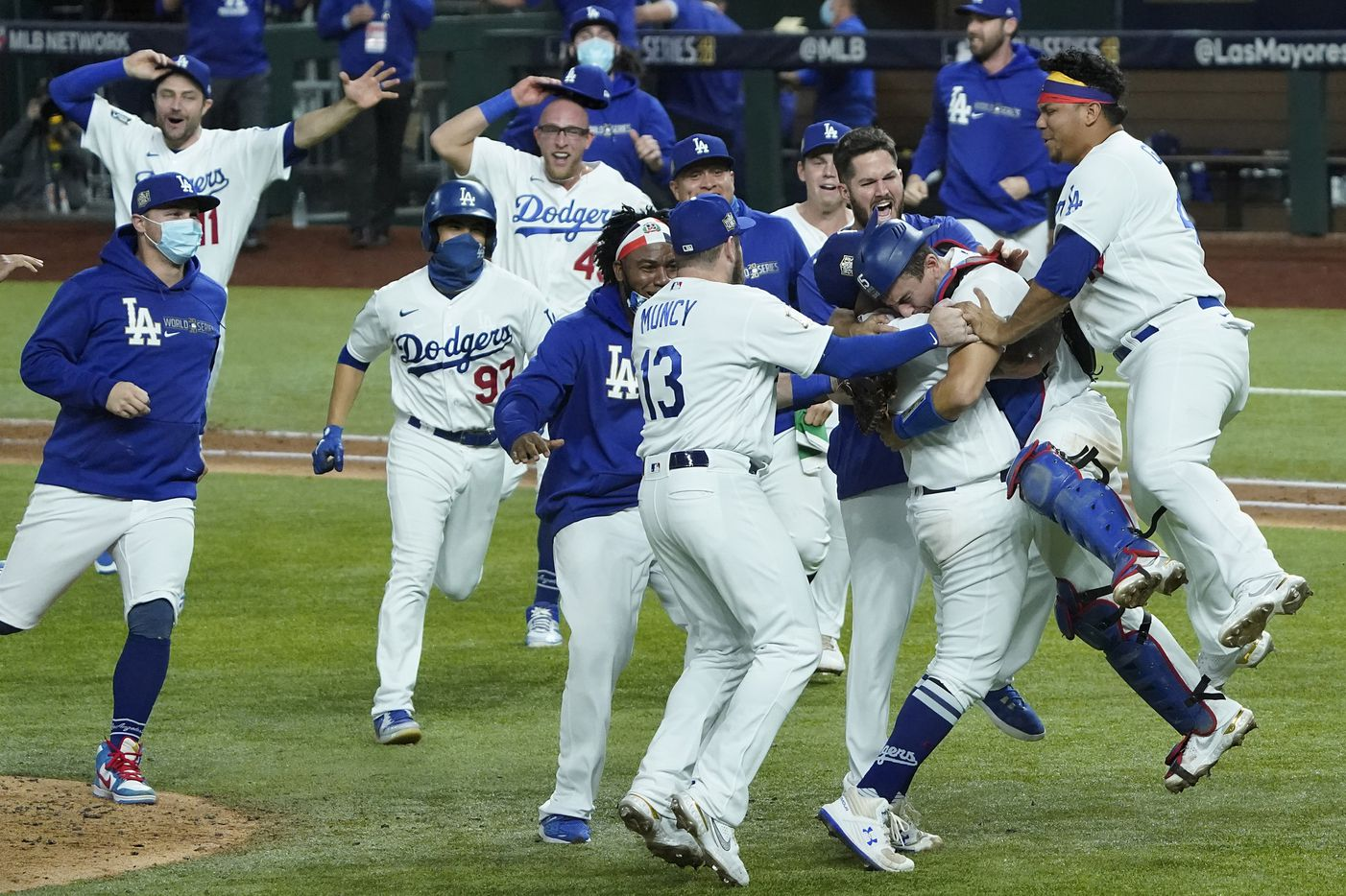 Los Angeles Dodgers players rush to join pitcher Julio Urias and catcher Austin Barnes as they celebrate the final out after defeating the Tampa Bay Rays in Game 6 of the World Series at Globe Life Field on Tuesday, Oct. 27, 2020.