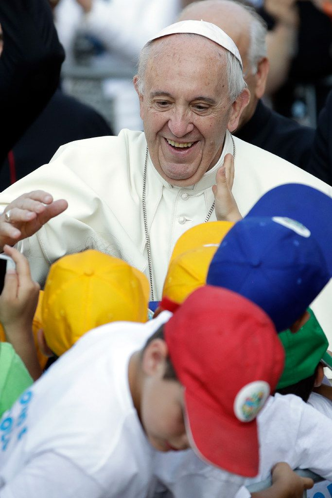 Pope Francis greets children Tuesday as he arrives at Bozzolo, near Cremona, northern Italy, to pray at the tomb of Don Primo Mazzolari.