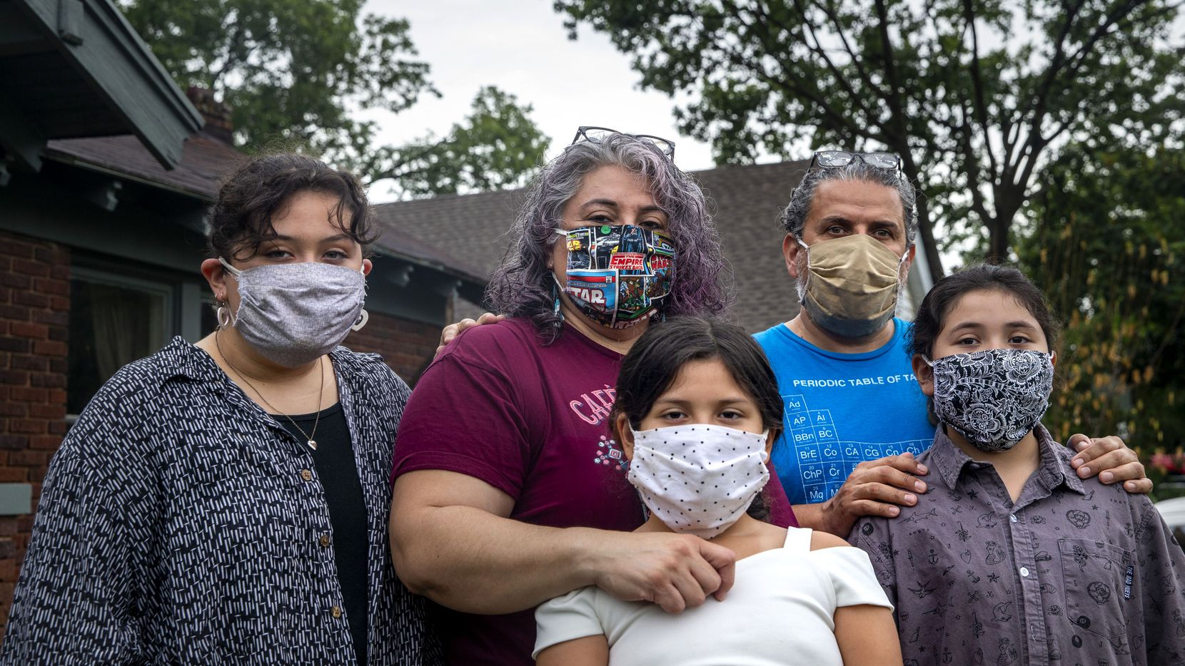 Ofelia Faz-Garza (center) and her husband Hector Garza (second from right) pose for a portrait with their daughters — from left, Meztli, 15, Paloma, 8, and Lila, 10 —outside their home in Oak Cliff on Tuesday, June 23, 2020.