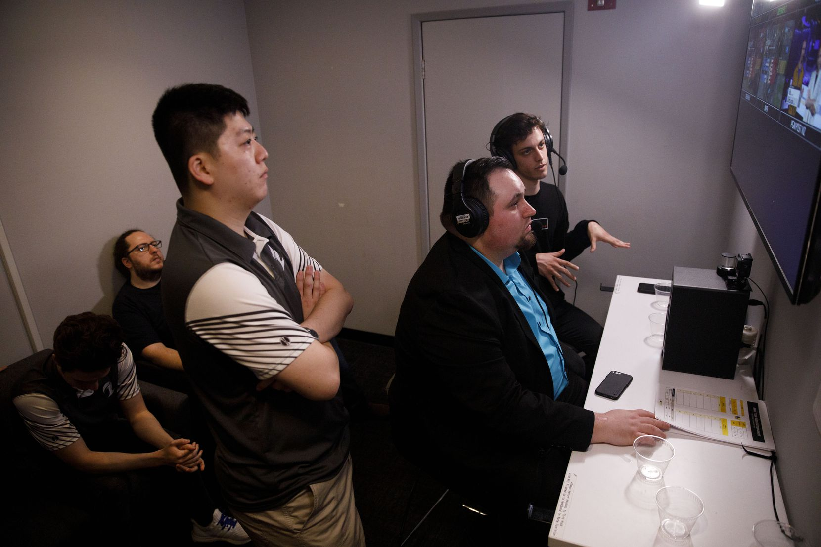 """Head coach Aaron """"Aero""""Atkins, center, Kang """"Vol'Jin"""" Min-Gyu, left, and Julien """"daemoN"""" Ducros watch their team from the backstage dugout during the Overwatch League team match between the Dallas Fuel and New York Excelsior on Saturday, June 29, 2019 in Burbank, Calif."""