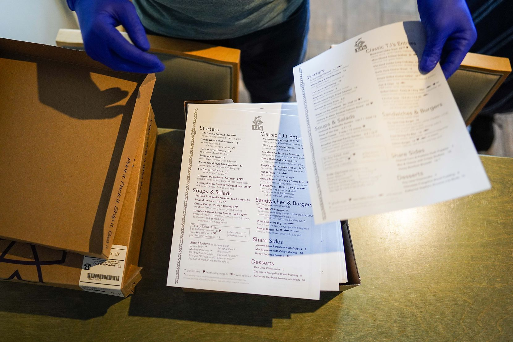 Bar manager Brett Martin unboxes new disposable menus at TJ's Seafood restaurant on Tuesday in Dallas. The restaurant has partnered with a testing company to test all of their employees for COVID-19, screen and train them. (Smiley N. Pool/The Dallas Morning News)