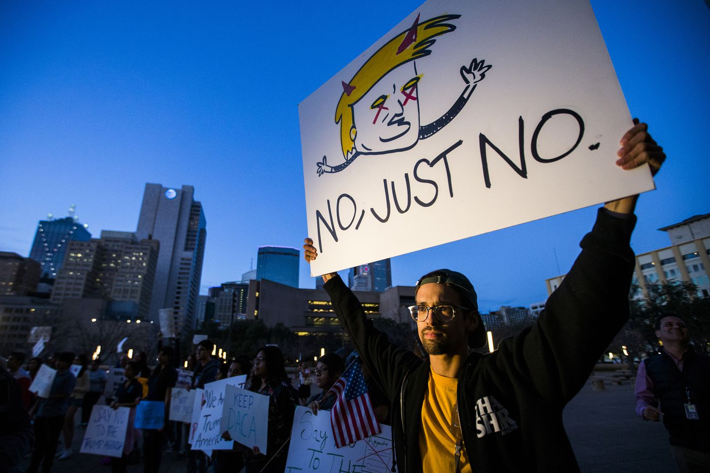 Jonathan Smith of Dallas holds a sign in opposition to the inauguration of Donald Trump during a rally at Dallas City Hall on Friday, Jan. 20, 2017, in Dallas.