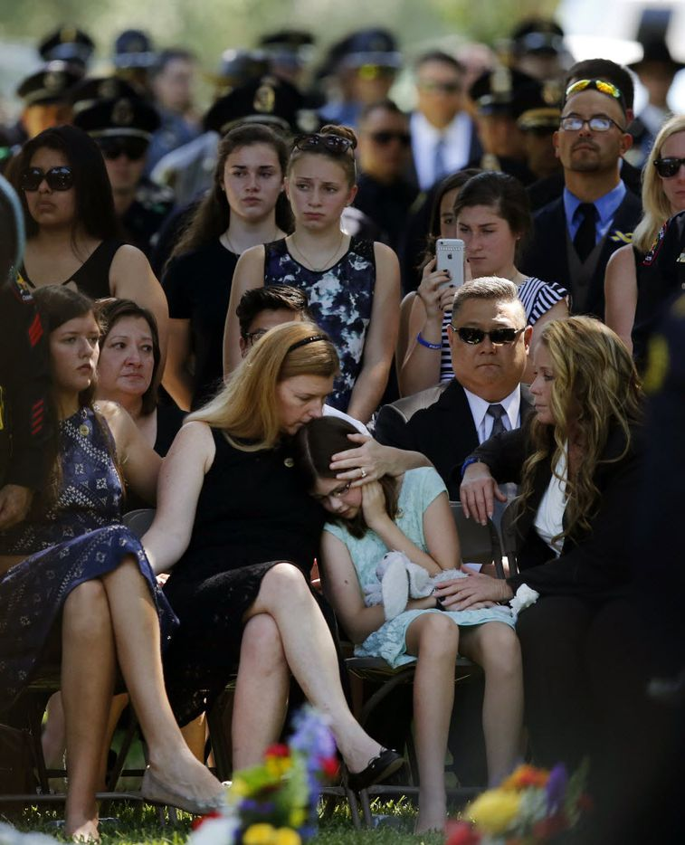 Heidi Smith comforts her daughter Caroline (right) fowling a 21 gun salute during a graveside service as her husband Dallas police Sgt. Michael Smith was laid to rest at the Restland Funeral Home and Cemetery in Dallas, Thursday, July 14, 2016. Her other daughter Victoria is seated on the left. Smith was gunned down in an ambush attack in downtown Dallas a week ago. Four Dallas police officers and one DART officer were killed. (Tom Fox/The Dallas Morning News)