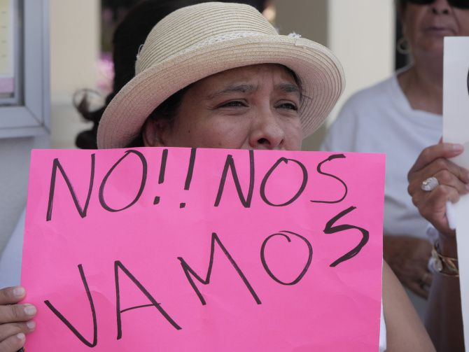 """Protester Florencia Navarro, a 24-year resident of the Dallas West Mobile Home/RV Park, held a sign that translates to """"we will not go"""" while demonstrating with other neighbors."""