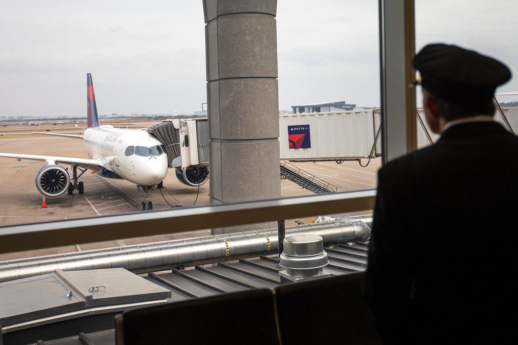 Delta's new Airbus A220-100 airplane attracts attention while parked at gate E15 of Terminal E at DFW Airport.