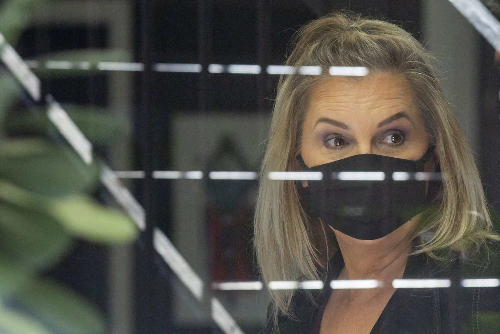 Shelley Luther glances out of the front window at her business, Salon ‡ la Mode, in Far North Dallas on Wednesday, April 29, 2020. (Lynda M. Gonzalez/The Dallas Morning News)