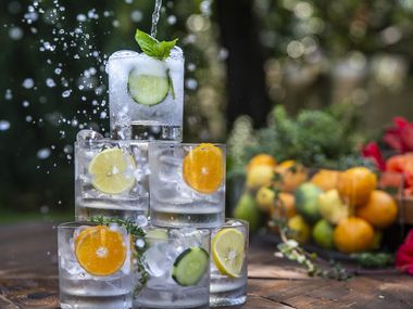 Tonic water splashes onto a stack of glasses.