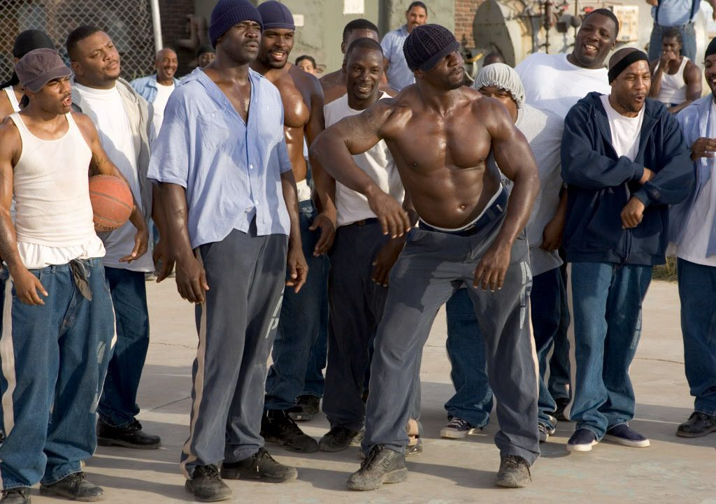 """Several inmates, including Megget (Nelly, left), Deacon Moss (Michael Irvin, center left, blue shirt) and Cheeseburger Eddy (Terry Crews, center right), are at first reluctant to join the football game against the guards in  """" The Longest Yard. """""""