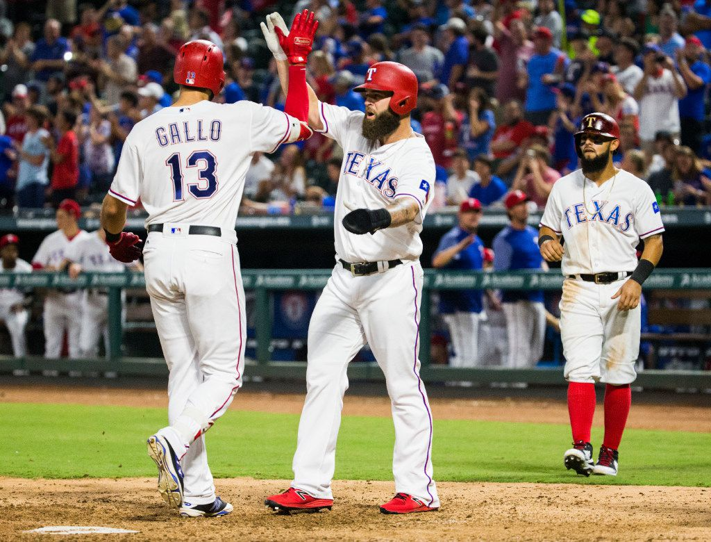 Texas Rangers third baseman Joey Gallo (13) high-fives first baseman Mike Napoli (5) after Gallo's home run brought in Gallo, Napoli and second baseman Rougned Odor (12) during the sixth inning of an MLB game between the Texas Rangers and the Seattle Mariners on Tuesday, August 1, 2017 at Globe Life Park in Arlington, Texas.  (Ashley Landis/The Dallas Morning News)