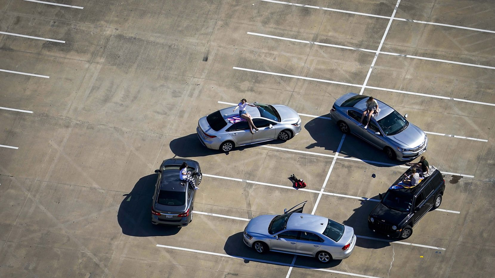 Young people gather in the parking lot of McKinney High School on Tuesday, March 24, 2020.