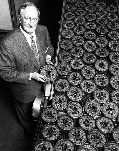 Bill McNutt Jr., President of the  Collin Street Bakery in Corsicana, stands near some of his small  fruitcakes as they move down the conveyer after being cooked.