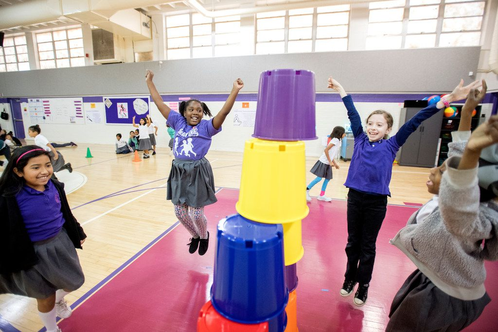 From left: Kayla Quiroga, 8; Ny'Angela Carrathus, 8; Caroline Fenlaw, 9; and Justice MacDonald, 8, celebrate after building a pyramid out of plastic buckets during a sport stacking event on Nov. 9, 2017, at Solar Preparatory School for Girls at James B. Bonham in Dallas.