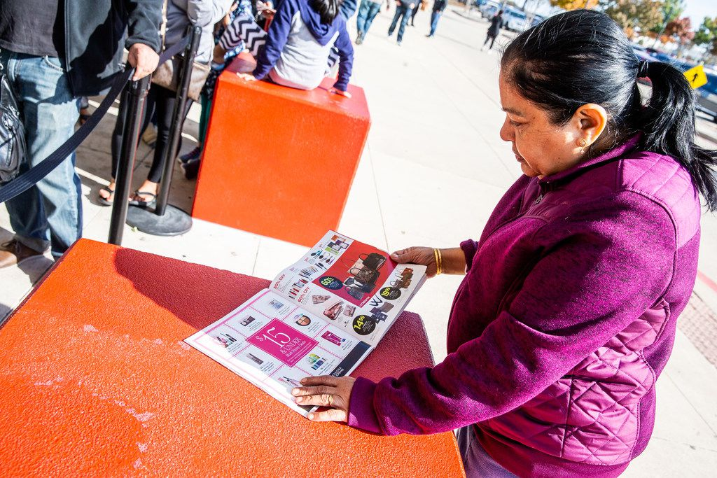 Apart Upabhay looks through a J.C. Penney catalog as she waits in line before Black Friday shopping outside the store in Fairview.
