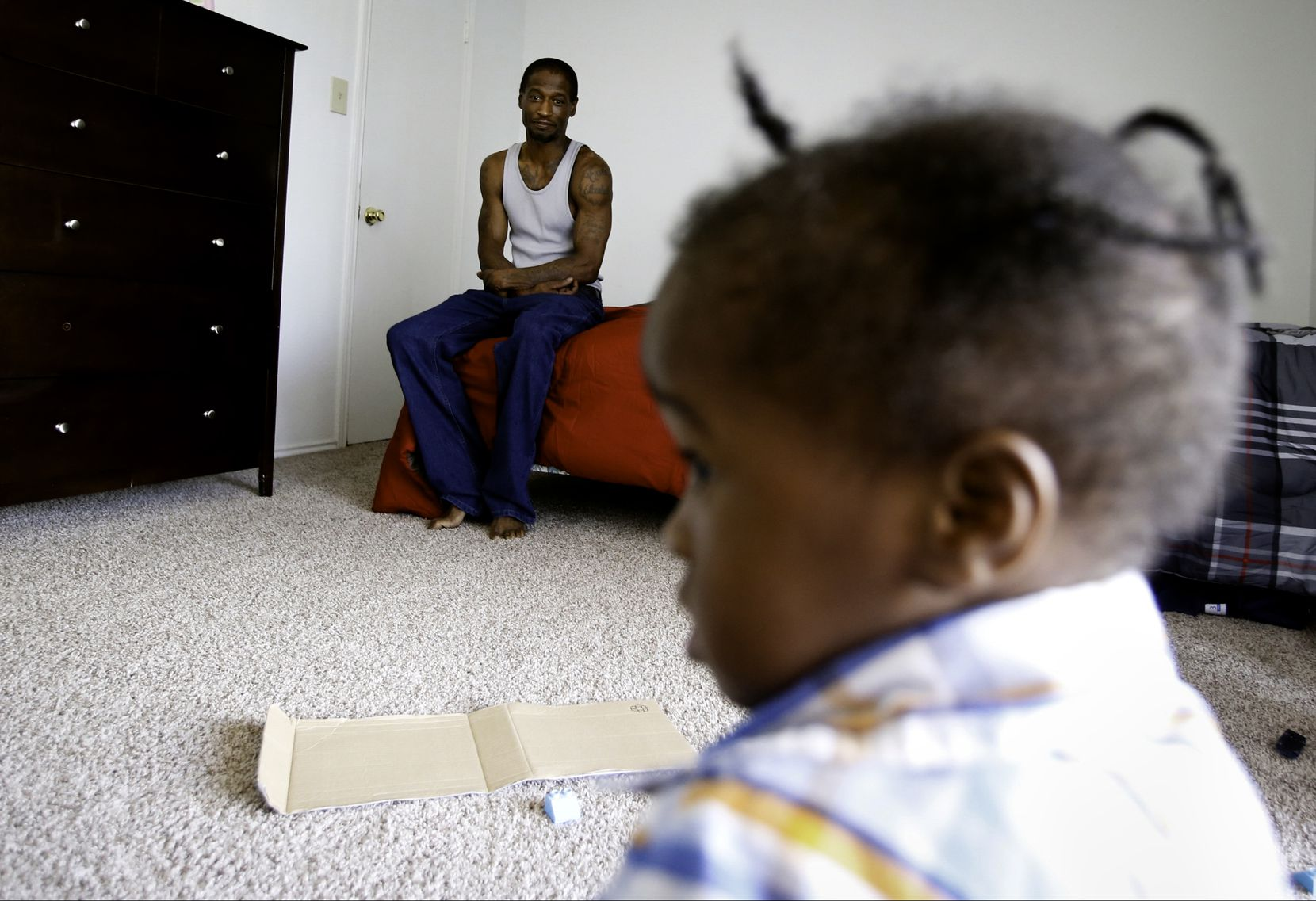 Joshua Miller watches Jordan play in their new apartment. After weeks of living in a room at The Family Place's men's shelter, Miller says, having a place for him and his son feels like a weight has been lifted off his shoulders. (Tailyr Irvine/The Dallas Morning News)