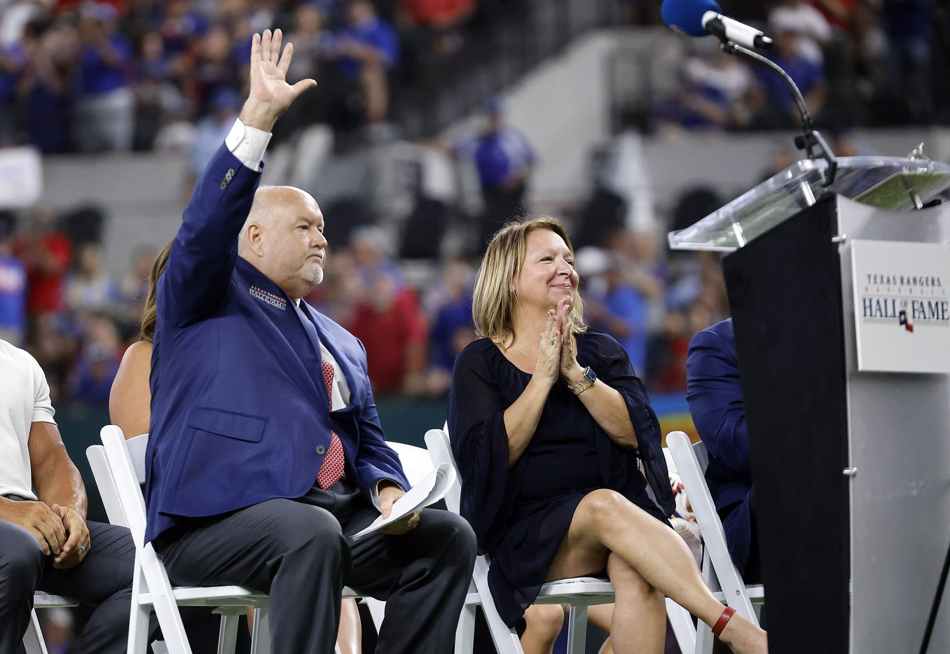 Texas Rangers executive vice president and public address announcer Chuck Morgan waves t the crowd after delivering his Texas Rangers Baseball Hall of Fame induction speech at Globe Life Field in Arlington, Saturday, August 14, 2021. His wife Starr is by his side. (Tom Fox/The Dallas Morning News)