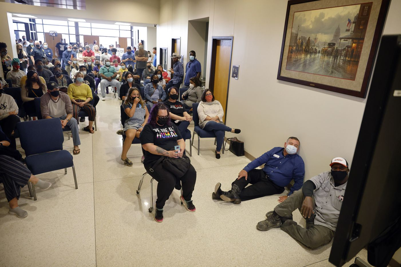 """From the hallway, an overflow crowd of parents and supporters watched a closed-circuit video feed of the Aledo ISD school board meeting, Monday, April 19, 2021. The people came to support the parents of two African-American boys who were targeted in a racist Snapchat group with multiple names, including """"Slave Trade"""" and another that included a racial slur. (Tom Fox/The Dallas Morning News)"""
