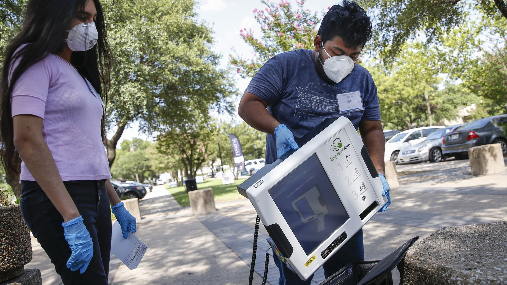 High school poll workers Sebastian Roman (right), 18, and Diana Paulin, 18, put away an electronic voting machine as they work a curbside voting lane during early voting at Beckley Courthouse on July 9, 2020 in Dallas. (Ryan Michalesko/The Dallas Morning News)