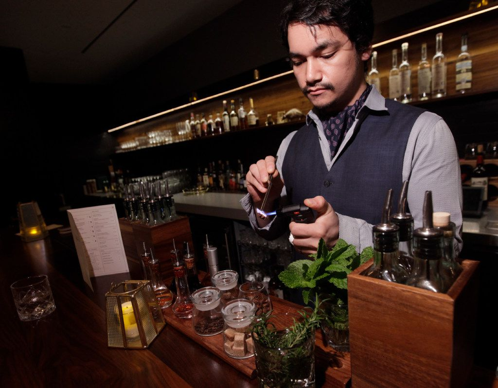 Bartender George Kaiho mixes drinks at Jettison in Dallas, on Dec. 7, 2016.