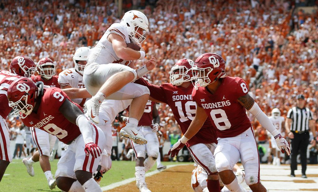 FILE - Texas Longhorns quarterback Sam Ehlinger (11) leaps over Oklahoma Sooners linebacker Kenneth Murray (9) to score a touchdown during the second half of play at the Cotton Bowl in Dallas on Saturday, October 6, 2018. Oklahoma Sooners linebacker Curtis Bolton (18) and Oklahoma Sooners safety Kahlil Haughton (8) watch as he prepares to land. Texas Longhorns defeated Oklahoma Sooners 48-45. (Vernon Bryant/The Dallas Morning News)